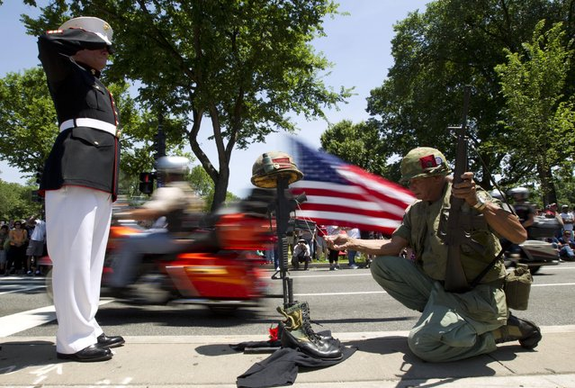 Marine Time Chamber and Army Eric Cantu salutes as motorcycles drive past during the annual Rolling Thunder parade ahead of Memorial Day in Washington, Sunday, May 24, 2015. (Photo by Jose Luis Magana/AP Photo)