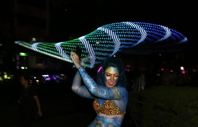 A woman spins a flashing hula hoop as she prepares for the annual Gay and Lesbian Mardi Gras parade in Sydney, Saturday, March 4, 2017. (Photo by Rick Rycroft/AP Photo)