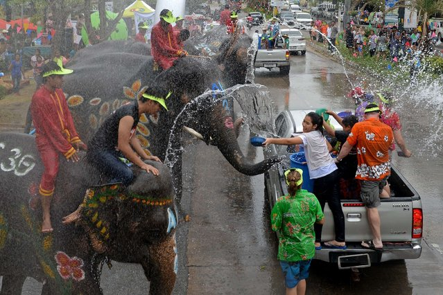 Thai people and foreign tourists (R) take part in water battles with elephants as they join celebrations marking the Songkran Festival in Ayutthaya province on April 12, 2013. (Photo by Pornchai Kittiwongsakul/AFP Photo)