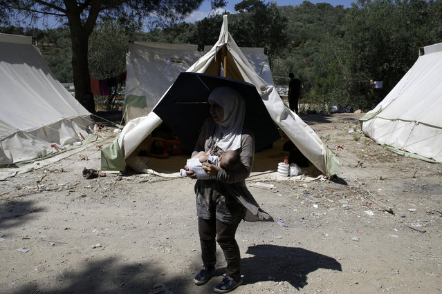 A Syrian mother holds her ten month-old son Ahmad after their arrival at a refugee and migrant camp in the village of Moria on the northeastern Greek island of Lesvos on Wednesday, June 17, 2015. The Aegean island has borne the brunt of a huge influx of migrants from the Middle East, Asia and Africa crossing from Turkey to nearby Greek islands. More than 50,000 migrants have arrived in Greece so far this year. (AP Photo/Thanassis Stavrakis)