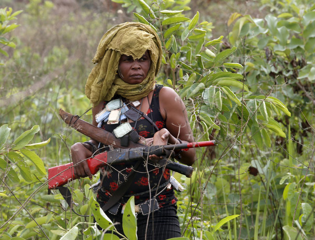 A female member of the anti-balaka, a Christian militia, patrols with other militiamen outside village of Zawa April 8, 2014. (Photo by Goran Tomasevic/Reuters)