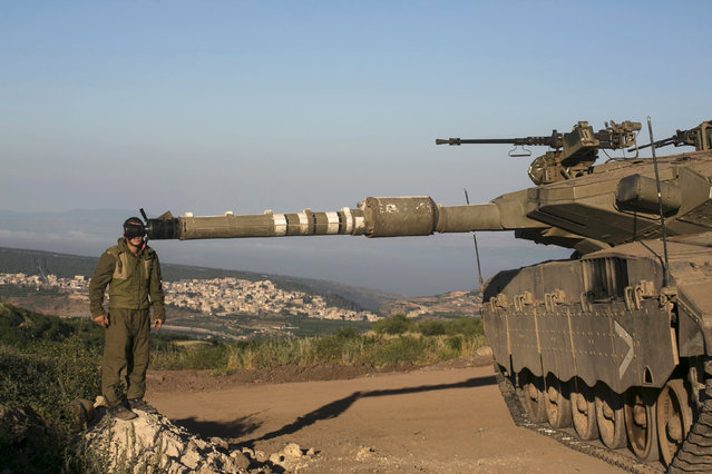 An Israeli soldier adjusts sights on a tank in the Israeli-occupied Golan Heights, near the ceasefire line between Israel and Syria, June 17, 2015. Israel signaled readiness on Tuesday to intervene if Syrian refugees were to throng to its armistice line on the Golan Heights, after Israel's Druze Arab minority stepped up a public campaign to help brethren caught up in the civil war next door. REUTERS/Baz Ratner