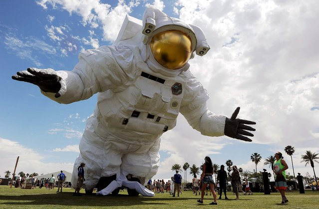 "The ""Escape Velocity"" moving sculpture by artist group Poetic Kinetics looms over Coachella festivalgoers on the Empire Polo Field, on the first day of the 2014 Coachella Music and Arts Festival in Indio, California, on April 11, 2014. (Photo by Chris Pizzello/Invision)"