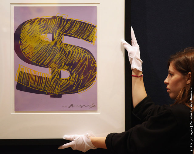 A gallery assistant adjusts a print of an Andy Warhol artwork estimated to fetch 20,000 GBP in Bonhams auction house