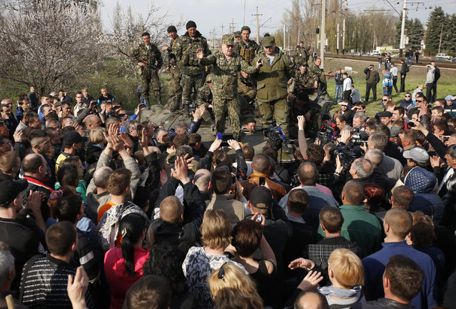 Ukrainian soldiers standing on a combat vehicle try to negotiate with pro-Russian protesters in Kramatorsk, in eastern Ukraine April 16, 2014. Fifteen armoured troop carriers full of paratroopers were surrounded and halted by a pro-Russian crowd at a town near an airbase. They were allowed to retreat only after the soldiers handed the firing pins from their rifles to a rebel commander. (Photo by Marko Djurica/Reuters)