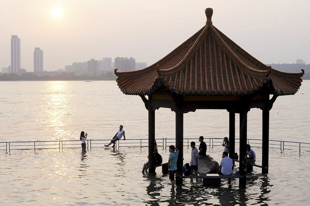 Tourists take pictures near a pavilion flooded by the swollen Yangtze River in Wuhan, Hubei province, June 19, 2015. (Photo by Reuters/China Daily)
