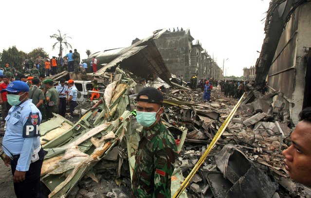 Rescuers search for victims the site where an Indonesian Air Force cargo plane crashed in Medan, North Sumatra, Indonesia, Tuesday, June 30, 2015. (Photo by Binsar Bakkara/AP Photo)