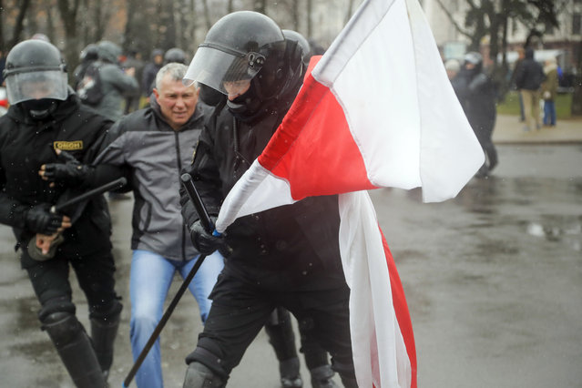 A Belarus policeman carries an opposition flag as other detain a protester during an opposition rally in Minsk, Belarus, Saturday, March 25, 2017. (Photo by Sergei Grits/AP Photo)
