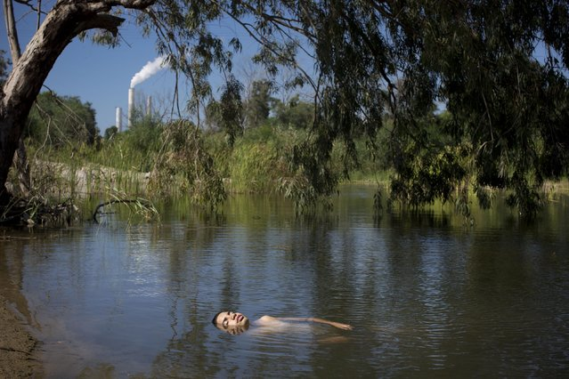 In this Sunday, June 21, 2015 photo, an Israeli youth bathes in a stream next to kibbutz Zikim, on the Israel-Gaza border. A year after the Gaza war, the community in southern Israel, long battered by rockets from the Hamas-run territory next door, has slowly recovered and is even seeing a quiet boom. (Photo by Oded Balilty/AP Photo)