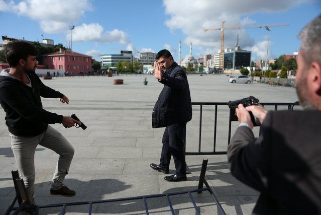 Plain clothes police officers point their guns at an assailant who attempted to shoot prominent Turkish journalist Can Dundar, outside a courthouse in Istanbul, Turkey May 6, 2016. (Photo by Can Erok/Reuters/Cumhuriyet)