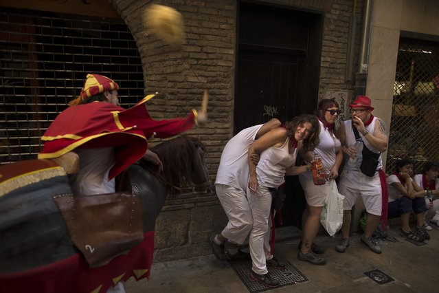A man representing a medieval horse rider hits revelers with a whip during the procession of Cabezudos figures on the opening of the 2015 San Fermin fiestas in Pamplona, Spain, Monday, July 6, 2015. (Photo by Andres Kudacki/AP Photo)