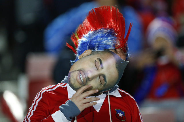 A fan holds a mask of Chile's Arturo Vidal  during a Copa America semifinal soccer match at the National Stadium in Santiago, Chile, Monday, June 29, 2015. (Photo by Andre Penner/AP Photo)