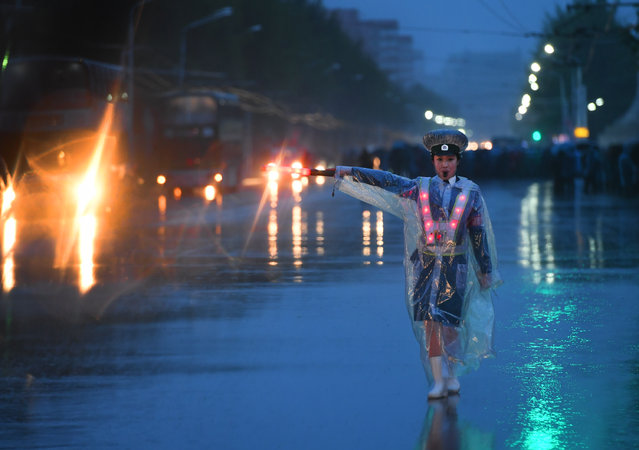 A woman directs traffic in the pouring rain in Pyongyang, North Korea on May 3, 2016. The city is preparing for the Workers' Party Congress starting on May 6th.  It will be the first time since 1980 that the ruling party has convened. (Photo by Linda Davidson/The Washington Post)
