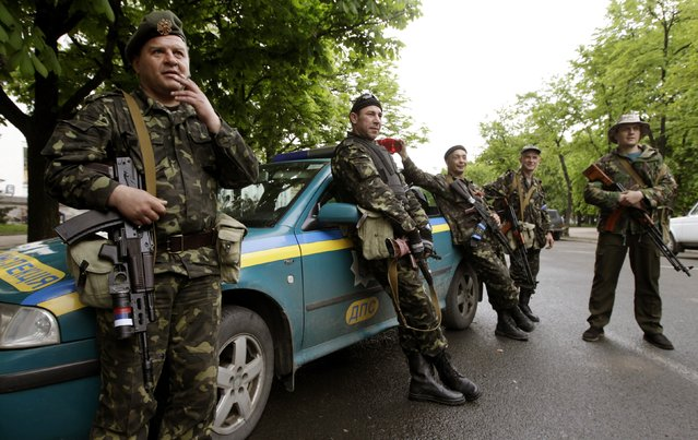 Armed pro-Russian activists stand near the seized regional government headquarters in Luhansk, eastern Ukraine, May 3, 2014. (Photo by Vasily Fedosenko/Reuters)