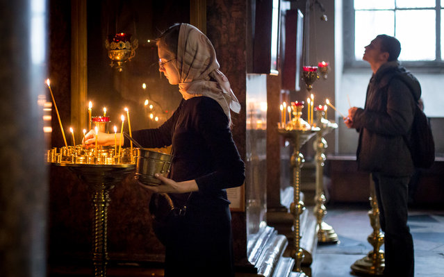 """Lighting Candles"". An Orthodox Russian woman who works at Kazan Cathedral clears out old candles and cleans off old wax. Another young devout lights up a candle in the background as a form of prayer to God, an important tradition in Orthodox worship. Photo location: St Petersburg, Russia. (Photo and caption by Justin Tiew/National Geographic Photo Contest)"