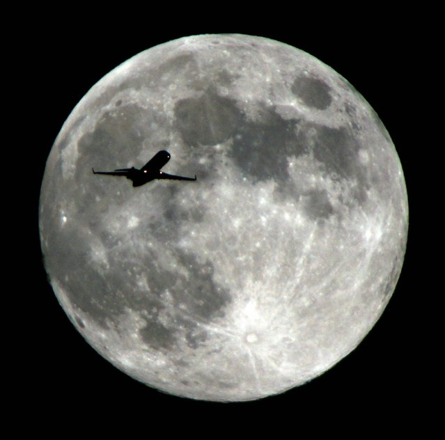 An airlines jet plane approaching Los Angeles International Airport crosses the moon as seen from Monterey Park Calif., Wednesday night, September 18,  2013. The Harvest Moon is the full moon that falls closest to the autumnal equinox, which marks the beginning of fall in the Northern Hemisphere. (Photo by Nick Ut/AP Photo)