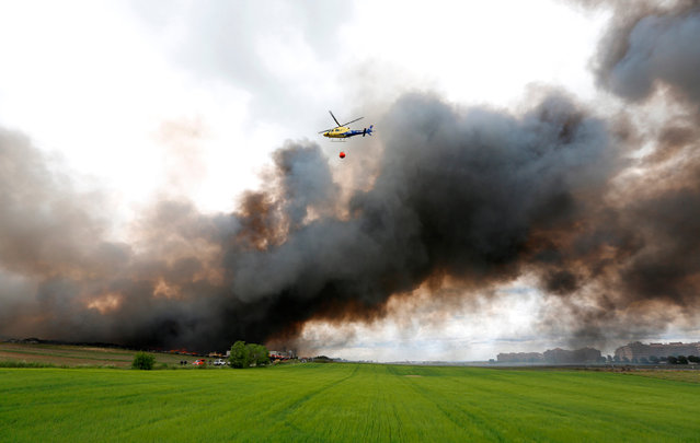 An helicopter prepares to throw water over a fire at a tire dump near a residential development in Sesena, south of Madrid, Spain, May 13, 2016. (Photo by Sergio Perez/Reuters)