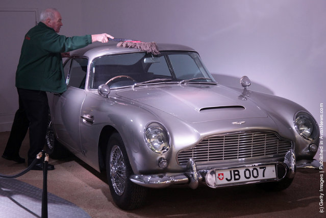 A member of the musuem team attends to a Aston Martin DB5 used in the James Bond film Goldfinger and being displayed at the Bond In Motion exhibition