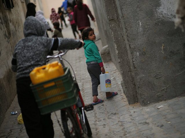 A Palestinian girl carries a potable water container after filling it from a public tap in Jabaliya refugee camp in the northern Gaza Strip January 24, 2017. (Photo by Mohammed Salem/Reuters)