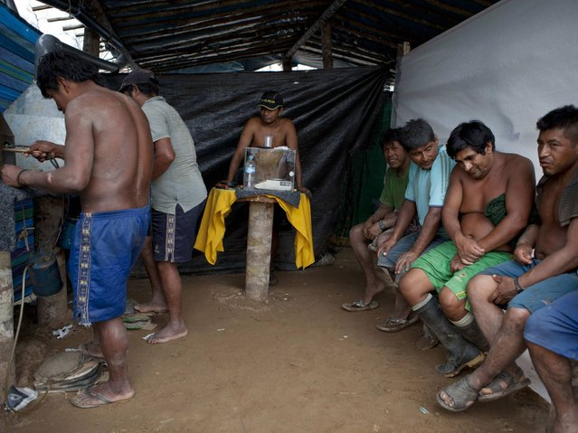 Wildcat miners wait their turn to melt their amalgam of gold and mercury to burn off the mercury in the temporary home of a gold buyer in La Pampa in Peru's Madre de Dios region. (Photo by Rodrigo Abd/AP Photo)