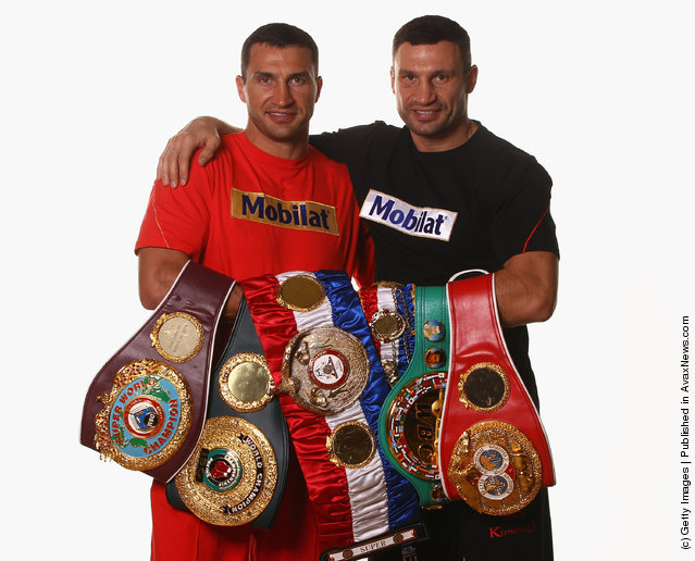 Wladimir Klitschko (L) and his brother Vitali Klitschko pose with their championship belts including the WBO Super World Champion belt, 'THE RING' Magazine belt, WBC belt und IBF belt during a photocall at Hotel Stangwirt