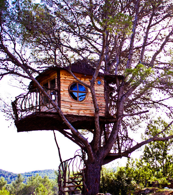 The Witch House, Ibiza, Spain. An Aleppo pine hosts an eclectic creation using locally sourced materials. The round windows were built on-site after the busilder left the island by a talented mason turned carpenter. (Photo by Pete Nelson)