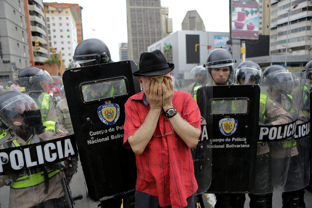 An opposition supporter covers his face to protect himself from tear gas during clashes with riot police in a rally to demand a referendum to remove President Nicolas Maduro in Caracas, Venezuela, May 18, 2016. (Photo by Marco Bello/Reuters)