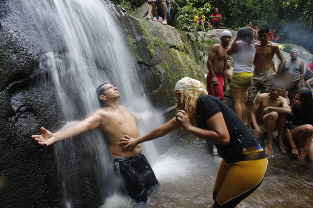 """In this photo taken October 12, 2019, a spiritual guide known as a """"madrina"""" performs a ritual on a man training to become a medium to receive spirits into his body on Sorte Mountain where followers of indigenous goddess Maria Lionza gather annually in Venezuela's Yaracuy state. The tradition is hundreds of years old and draws on elements of the Afro-Caribbean religion Santeria and indigenous rituals, as well as Catholicism. (Photo by Ariana Cubillos/AP Photo)"""