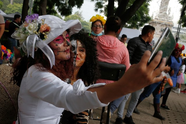Women wearing Catrina makeup take a selfie before the parade down Mexico City's iconic Reforma avenue during celebrations for the Day of the Dead, Saturday, October 26, 2019. (Photo by Ginnette Riquelme/AP Photo)