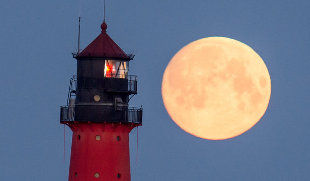 The full moon above a lighthouse in Westerhever, Germany on April 21, 2016. (Photo by Daniel Reinhardt/DPA)