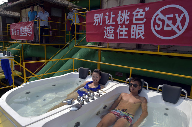 In this photo taken Friday July 17, 2015, visitors to a water park enjoy massage tubs near a banner warning visitors against having s*x while using the facilities, in southwestern China's Chongqing Municipality. A recent s*x video shot in a fitting room that had gone viral online have raised questions over social morals and ethics. (Photo by Chinatopix via AP Photo)