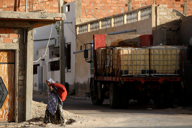A woman walks past a truck loaded with containers in the town of Remada, Tunisia  April 11, 2016. (Photo by Zohra Bensemra/Reuters)
