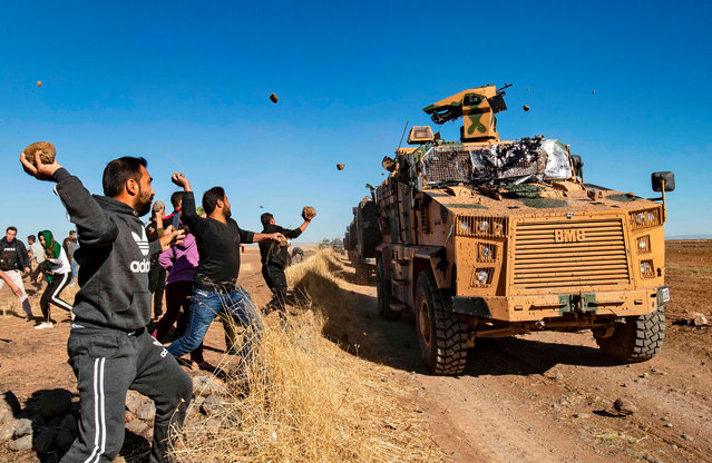Kurdish demonstrators hurl rocks at a Turkish military vehicle on November 8, 2019, during a joint Turkish-Russian patrol near the town of Al-Muabbadah in the northeastern part of Hassakah on the Syrian border with Turkey. (Photo by Delil Souleiman/AFP Photo)