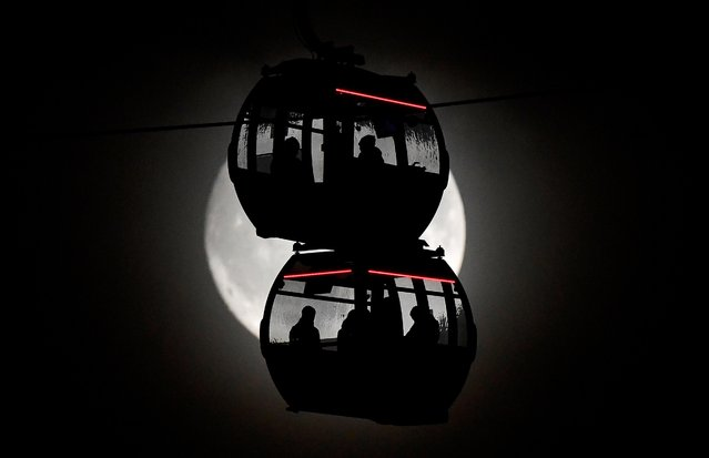 Passengers are seen silhouetted by the moon as they ride on the Emirates Air Line cable car over the River Thames in London, Britain, November 11, 2019. (Photo by Toby Melville/Reuters)