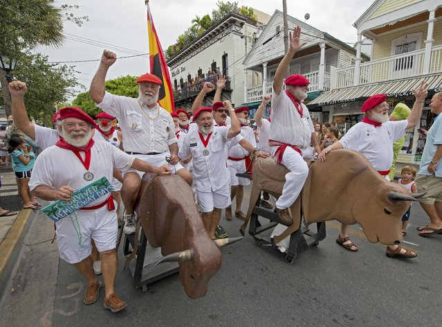"Participants in the annual Ernest Hemingway Look-Alike Contest proceed on Duval Street during the annual ""Running of the Bulls"" in this handout photo provided the Florida Keys News Bureau, in Key West, Florida, July 25, 2015,  The whimsical and much safer answer to the event's namesake in Pamplona, Spain, was staged as a facet of the island city's annual Hemingway Days festival that ends Sunday. Hemingway lived and wrote in Key West throughout the 1930s. (Photo by Andy Newman/Reuters/Florida Keys News Bureau)"