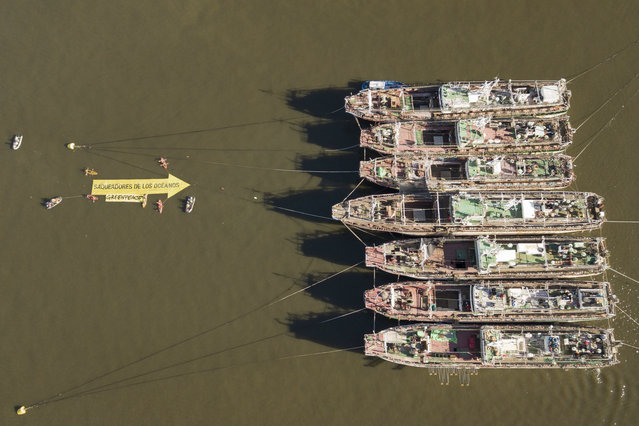 """In this aerial handout picture released by Greenpeace, activists of the non-governmental environmental organization display a 25 mts long arrow that reads """"Looters of the Oceans"""" pointing to South Korea's fishing vessels Agnes 103 y Agnes 107 anchored at the port of Montevideo on October 31, 2019, as part of a campaign to denounce destructive fishery activities in the Argentine Sea. - According to Greenpeace, the Argentine Sea is endangered by industrial fishing that destroys the home of the southern right whale (Eubalaena australis) and other iconic species. Fishing vessels border the Argentine Sea taking advantage of the lack of regulation to fish indiscriminately in the South Atlantic, leaving it on the verge of collapse. (Photo by HO/Greenpeace/AFP Photo)"""