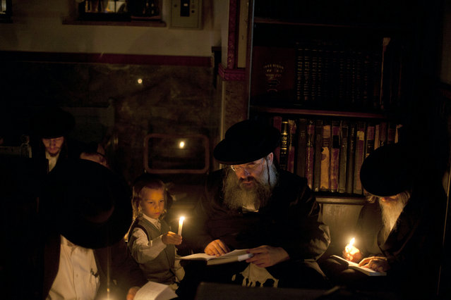 Ultra Orthodox Jews light candles and pray on the floor as they read from the book of Eicha (book of Lamentations) as they mark Tisha Be'ave at a synagogue in the Mea Shearim neighborhood on July 26, 2015 in Jerusalem, Israel. Tisha Be'ave is an annual fast day in Judaism which commemorates the anniversary of a number of disasters in Jewish history, primarily the destruction of both the First and Second Temples in Jerusalem. (Photo by Lior Mizrahi/Getty Images)