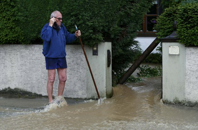 A man speaks on the phone as water runs through his garden in the flooded Bavarian village of Triftern east of Munich, Germany, June 1, 2016. (Photo by Michaela Rehle/Reuters)