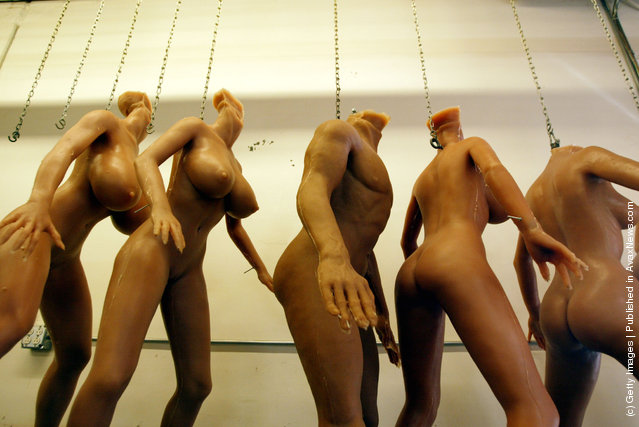 Unfinished silicone RealDoll s*x dolls hang from chains at the Abyss Creations factory