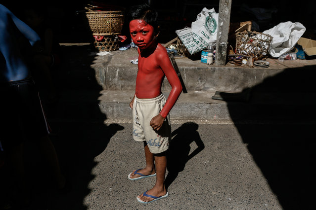 A boy dries the paint in the sun as he prepares for Grebeg Ritual on June 25, 2014 in Tegallalang Village, Gianyar, Bali, Indonesia. During the biannual ritual, young members of the community parade through the village with painted faces and bodies to ward off evil spirits. (Photo by Putu Sayoga/Getty Images)