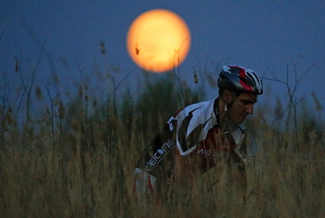 A cyclist rides his mountain bike as a full moon, known as the Blue Moon, rises in a park in Rome, Italy, July 31, 2015. (Photo by Max Rossi/Reuters)