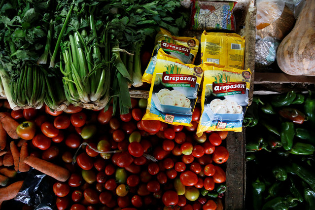 Packages of corn flour that are made in Colombia are displayed among vegetables at a stall at a market in La Fria, Venezuela, June 2, 2016. (Photo by Carlos Garcia Rawlins/Reuters)