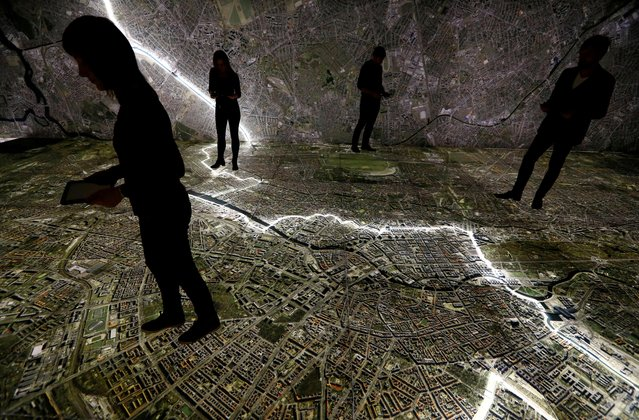 """Museum staff members walk with mobile devices over a giant illuminated aerial photograph of Berlin, including the marked course of the Berlin Wall and places related to the former East German Ministry for State Security (MfS), known as the Stasi, at the exhibition """"The Stasi in Berlin"""" inside former Stasi prison in Hohenschoenhausen, Berlin, Germany, March 27, 2019. (Photo by Fabrizio Bensch/Reuters)"""