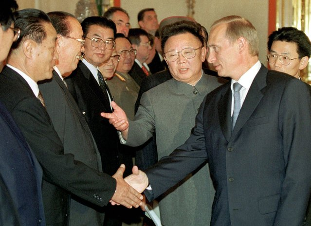 North Korean leader Kim Jong Il, center, introduces his staff to Russian President Vladimir Putin, right, prior to their talks in Moscow's Kremlin, Saturday, Aug. 4, 2001. Putin and Kim opened talks in the Kremlin Saturday that were expected to renew economic and other ties between the two once ideological allies. (Photo by Sergi Velichkin/AP Photo/ITAR-TASS/Presidential Press Service)