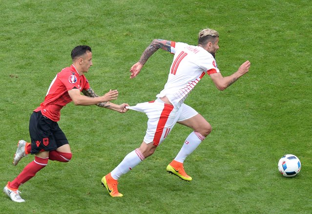Albania's midfielder Ergys Kace (L) pulls down the shorts of Switzerland's midfielder Valon Behrami during the Euro 2016 group A football match between Albania and Switzerland the Bollaert-Delelis Stadium in Lens on June 11, 2016. (Photo by Denis Charlet/AFP Photo)