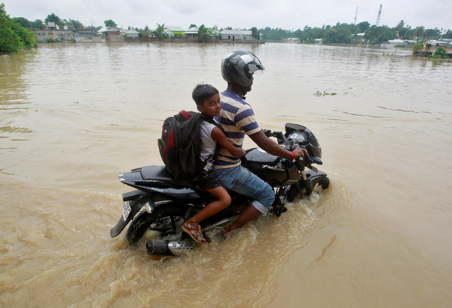 A man rides a motorcycle through a flooded road after heavy rains on the outskirts of Agartala, India June 20, 2017. (Photo by Jayanta Dey/Reuters)
