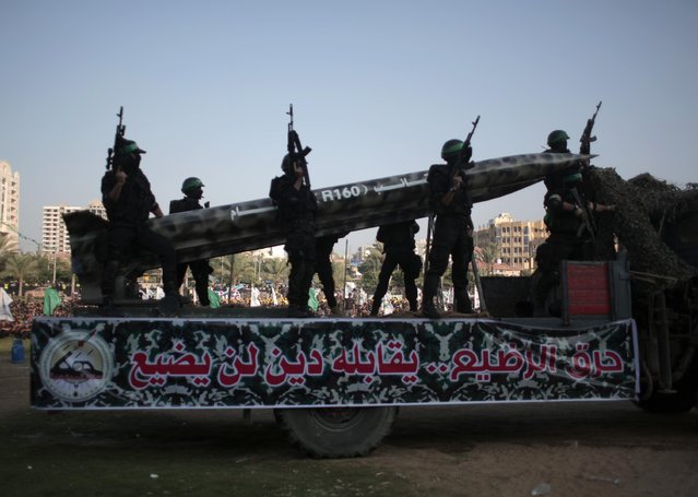 "Palestinian Hamas masked gunmen display a homemade rocket on a truck with Arabic writing that reads, ""Burning the infant is a loan, that will not get lost"", during a graduation ceremony of the Hamas, Liberation Youth, military summer camp, in Gaza City, Wednesday, August 5, 2015. (Photo by Khalil HamraAP Photo)"
