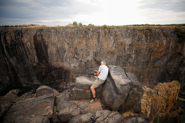 Visitors take pictures before dry cliffs following a prolonged drought at Victoria Falls, Zimbabwe, December 4, 2019. (Photo by Mike Hutchings/Reuters)