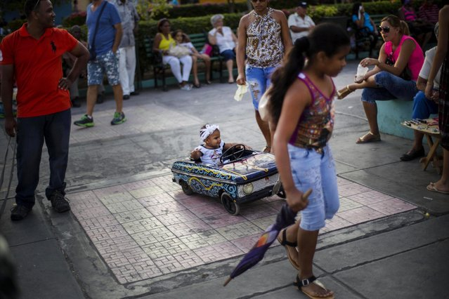 In this March 22, 2015 photo, a girl pulls a toddler in an antique toy car at a park in Santiago, Cuba. The toddler's parents paid a vendor, who sells rides in the car, to take her on a ride through the park. Residents say the government has dramatically eased the difficulties of starting a small business, allowing thousands more permits for businesses ranging from motorcycle taxis to air-conditioner repair workshops. (Photo by Ramon Espinosa/AP Photo)
