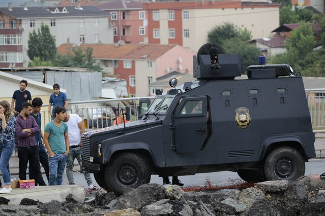People stand next to an armed vehicle of the police special forces outside a police station after an attack in Istanbul, Turkey, August 10, 2015. (Photo by Huseyin Aldemir/Reuters)
